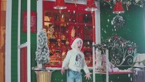 Λίγο χαμογελώντας αγόρι σε ένα ένα πλεκτό πουλόβερ Χριστουγέννων καπέλο και ρίχνει τα flos φιλμ μικρού μήκους