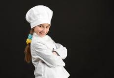 Λίγο χαμογελώντας κορίτσι στο άσπρο κοστούμι αρχιμαγείρων Στοκ εικόνα με δικαίωμα ελεύθερης χρήσης