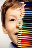Λίγο χαριτωμένο αγόρι με τα μολύβια χρώματος κλείνει επάνω να χαμογελάσει διανυσματική απεικόνιση