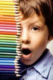 Λίγο χαριτωμένο αγόρι με τα μολύβια χρώματος κλείνει επάνω να χαμογελάσει απεικόνιση αποθεμάτων