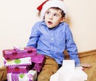 Λίγο χαριτωμένο αγόρι με τα δώρα Χριστουγέννων στο σπίτι κλείστε επάνω συναισθηματικό Στοκ εικόνες με δικαίωμα ελεύθερης χρήσης