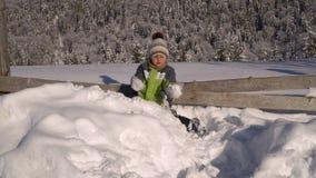 Λίγο χαριτωμένο αγόρι που παίζει στο χιόνι έξω το χειμώνα Στο υπόβαθρο είναι ένα χιονώδες δάσος που το αγόρι είναι ευτυχές απόθεμα βίντεο