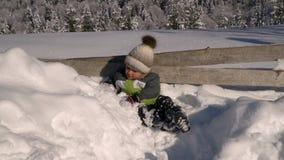 Λίγο χαριτωμένο αγόρι που παίζει στο χιόνι έξω το χειμώνα Στο υπόβαθρο είναι ένα χιονώδες δάσος που το αγόρι είναι ευτυχές αργός φιλμ μικρού μήκους