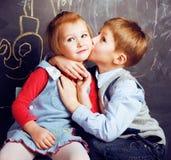 Λίγο χαριτωμένο αγόρι που φιλά το ξανθό κορίτσι στην τάξη στον πίνακα, πρώτη σχολική αγάπη, έννοια ανθρώπων τρόπου ζωής Στοκ φωτογραφία με δικαίωμα ελεύθερης χρήσης