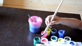 Λίγο χαριτωμένο αγόρι που χρωματίζει στο σπίτι την κάρτα στον πίνακα το αγόρι σύρει τα χρώματα και μια βούρτσα Στοχαστικός, σοβαρ απόθεμα βίντεο