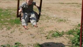 Λίγο χαριτωμένο αγόρι στην ταλάντευση γυαλιών στην ταλάντευση απόθεμα βίντεο