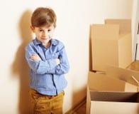 Λίγο χαριτωμένο αγόρι στο κενό δωμάτιο, remoove στο καινούργιο σπίτι το σπίτι μόνο μεταξύ των κιβωτίων κλείνει το επάνω χαμογελών Στοκ Φωτογραφία