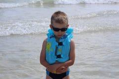 Λίγο χαριτωμένο αγόρι φαίνεται δυστυχισμένο στην παραλία στοκ εικόνες
