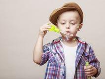 Λίγο χαριτωμένο αγόρι φυσά τις τράπεζες σαπουνιών Στοκ Φωτογραφία