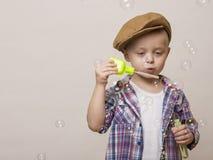 Λίγο χαριτωμένο αγόρι φυσά τις τράπεζες σαπουνιών Στοκ Εικόνα