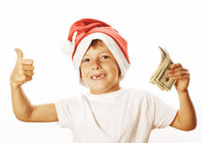 Λίγο χαριτωμένο αγόρι santas καπέλο που απομονώνεται στο κόκκινο με τα αμερικανικά δολάρια μετρητών φυλλομετρεί επάνω τον ευτυχή  Στοκ Εικόνες