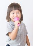 Λίγο χαριτωμένο ασιατικό μικρόφωνο εκμετάλλευσης κοριτσιών τραγουδώντας πέρα από το άσπρο υπόβαθρο Στοκ Φωτογραφίες