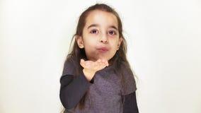 Λίγο χαριτωμένο εύθυμο κορίτσι στέλνει ένα φιλί αέρα και εξετάζει τη κάμερα, άσπρο υπόβαθρο 50 fps φιλμ μικρού μήκους