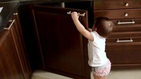 Λίγο χαριτωμένο κορίτσι ανοίγει ανεξάρτητα την πόρτα της κουζίνας σε σε αργή κίνηση απόθεμα βίντεο