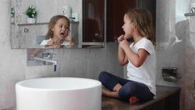 Λίγο χαριτωμένο κορίτσι βουρτσίζει τα δόντια της με το οδοντικό νήμα μπροστά από τον καθρέφτη φιλμ μικρού μήκους