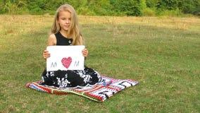 Λίγο χαριτωμένο κορίτσι γράφει τη λέξη MOM απόθεμα βίντεο
