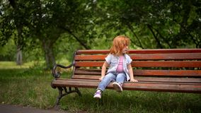 Λίγο χαριτωμένο κορίτσι κάθεται στον πάγκο φιλμ μικρού μήκους