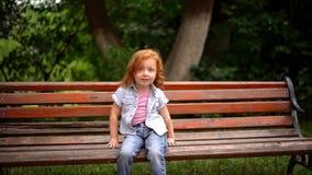 Λίγο χαριτωμένο κορίτσι κάθεται στον πάγκο απόθεμα βίντεο