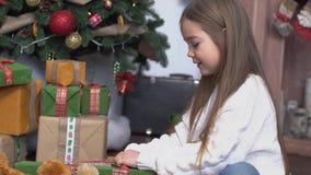 Λίγο χαριτωμένο κορίτσι με τη μακροχρόνια καφετιά συνεδρίαση τρίχας κοντά στο χριστουγεννιάτικο δέντρο και ανοικτός παρουσιάζει φιλμ μικρού μήκους