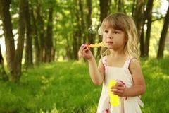 Λίγο χαριτωμένο κορίτσι με τις φυσαλίδες σαπουνιών Στοκ Εικόνες