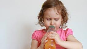 Λίγο χαριτωμένο κορίτσι πίνει το πορτοκαλί ποτό από ένα μπουκάλι Μωρό και πρόσφατα συμπιεσμένος χυμός, καταφερτζήδες, λεμονάδα, φ φιλμ μικρού μήκους
