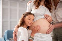 Λίγο χαριτωμένο κορίτσι που βάζει το αυτί της έγκυο σε tummy Στοκ Εικόνα