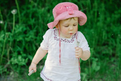 Λίγο χαριτωμένο κορίτσι που βγάζει από τη θέση που ήταν την πικραλίδα Στοκ φωτογραφία με δικαίωμα ελεύθερης χρήσης