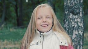 Λίγο χαριτωμένο κορίτσι που κάνει τα κέρατα και που γελά στο πάρκο φθινοπώρου φιλμ μικρού μήκους