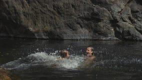 Λίγο χαριτωμένο κορίτσι που πηδά στο νερό της λίμνης βουνών στη μητέρα της απόθεμα βίντεο