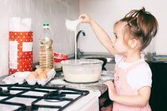 Λίγο χαριτωμένο κορίτσι που προετοιμάζει τη ζύμη στην κουζίνα στο σπίτι στοκ φωτογραφίες
