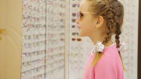 Λίγο χαριτωμένο κορίτσι που προσπαθεί στα γυαλιά ηλίου στο κατάστημα φιλμ μικρού μήκους