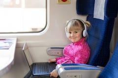 Λίγο χαριτωμένο κορίτσι που ταξιδεύει με το τραίνο Κινηματογράφος προσοχής παιδιών μέσω του lap-top με τα ακουστικά Δραστηριότητα Στοκ Εικόνα