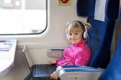 Λίγο χαριτωμένο κορίτσι που ταξιδεύει με το τραίνο Κινηματογράφος προσοχής παιδιών μέσω του lap-top με τα ακουστικά Δραστηριότητα Στοκ φωτογραφία με δικαίωμα ελεύθερης χρήσης
