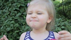 Λίγο χαριτωμένο κορίτσι που τρώει την κόκκινη σταφίδα απόθεμα βίντεο