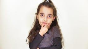 Λίγο χαριτωμένο κορίτσι που υποθέτει, που αναρωτιέται, που σκέφτεται και που εξετάζει τη κάμερα, πορτρέτο, άσπρο υπόβαθρο 50 fps φιλμ μικρού μήκους