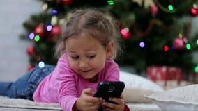Λίγο χαριτωμένο κορίτσι που χρησιμοποιεί το έξυπνο τηλέφωνο, μπροστά από το χριστουγεννιάτικο δέντρο Πυροβολισμός κινηματογραφήσε απόθεμα βίντεο