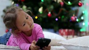 Λίγο χαριτωμένο κορίτσι που χρησιμοποιεί το έξυπνο τηλέφωνο, μπροστά από το χριστουγεννιάτικο δέντρο Πυροβολισμός κινηματογραφήσε φιλμ μικρού μήκους