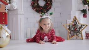 Λίγο χαριτωμένο κορίτσι σε ένα κόκκινο φόρεμα που χαμογελά βρίσκεται στο πάτωμα στο δωμάτιο με το ντεκόρ Χριστουγέννων απόθεμα βίντεο