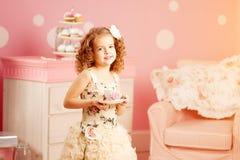 Λίγο χαριτωμένο κορίτσι σε ένα ρόδινο φόρεμα πίνει το τσάι με τα γλυκά στο γ Στοκ Φωτογραφία