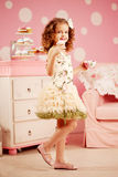 Λίγο χαριτωμένο κορίτσι σε ένα ρόδινο φόρεμα πίνει το τσάι με τα γλυκά στο γ Στοκ εικόνα με δικαίωμα ελεύθερης χρήσης