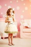 Λίγο χαριτωμένο κορίτσι σε ένα ρόδινο φόρεμα πίνει το τσάι με τα γλυκά στο γ Στοκ φωτογραφίες με δικαίωμα ελεύθερης χρήσης