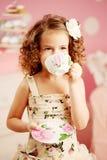 Λίγο χαριτωμένο κορίτσι σε ένα ρόδινο φόρεμα πίνει το τσάι με τα γλυκά στο γ Στοκ Εικόνες