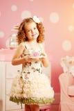 Λίγο χαριτωμένο κορίτσι σε ένα ρόδινο φόρεμα πίνει το τσάι με τα γλυκά στο γ Στοκ Εικόνα