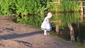 Λίγο χαριτωμένο κορίτσι στο φόρεμα που περπατά στην ακτή απόθεμα βίντεο