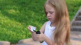 Λίγο χαριτωμένο κορίτσι φυσά τις φυσαλίδες στο πράσινο ηλιόλουστο πάρκο απόθεμα βίντεο