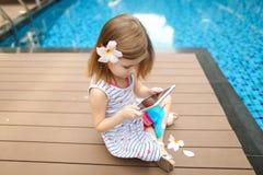 Λίγο χαριτωμένο κορίτσι χρησιμοποιεί την ταμπλέτα στην πισίνα υποβάθρου, wearin στοκ εικόνα