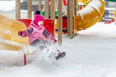 Λίγο χαριτωμένο κοριτσάκι που έχει τη διασκέδαση στην παιδική χαρά στο χειμώνα Χειμερινών αθλητισμού και ελεύθερου χρόνου παιδιών στοκ φωτογραφία με δικαίωμα ελεύθερης χρήσης