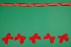 Λίγο χαριτωμένο κόκκινο υποκύπτει και μεταξωτή στροβιλισμένη κορδέλλα στο πράσινο backround με ένα διάστημα για το κείμενο στοκ εικόνες