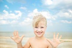 Λίγο χαριτωμένο ξανθό κορίτσι που έχει τη διασκέδαση στην παραλία στοκ εικόνα
