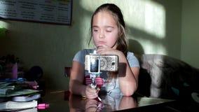 Λίγο χαριτωμένο ξανθό κορίτσι που μιλά σε κινητό κατοχή της τηλεοπτικής κλήσης στο έξυπνο τηλέφωνο φιλμ μικρού μήκους